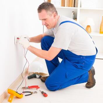 Installatør tester strømniveauet i en stikkontakt i en bolig